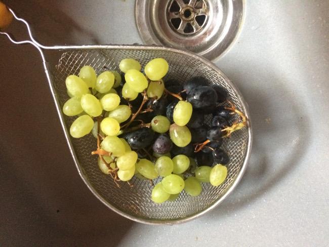 Lavaggio uva sotto l'acqua corrente